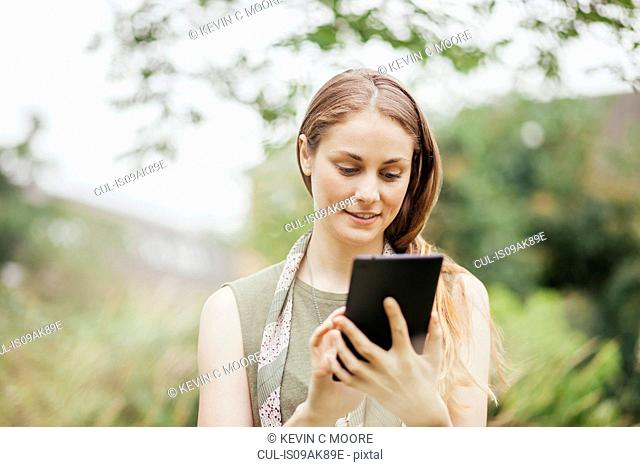 Young woman using touchscreen on digital tablet in field