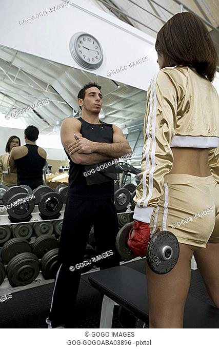 Personal trainer talking to woman at a gym