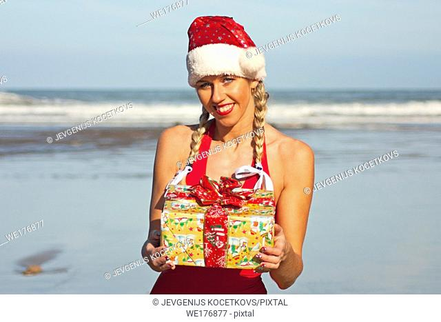 Santa girl with christmas gift on the beach