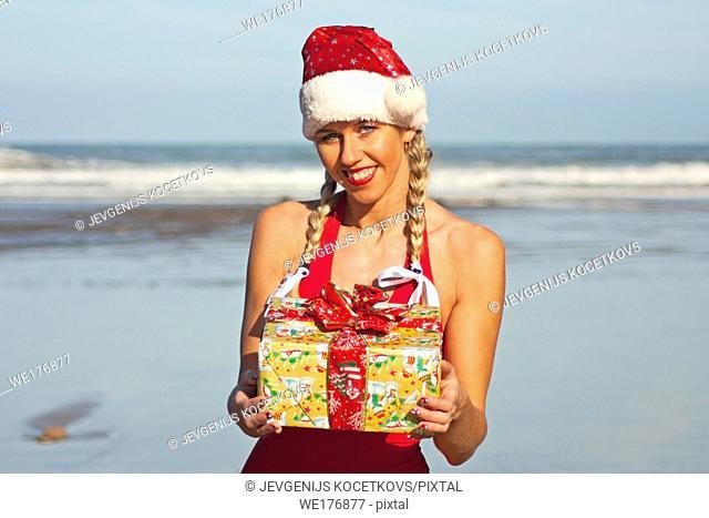 Santa girl with christmas gift on the beach
