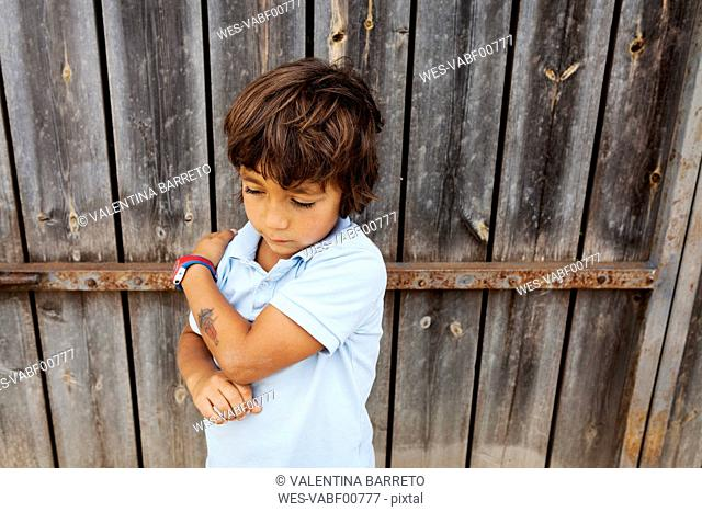 Serious little boy leaning against old wooden door