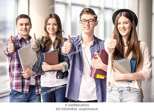 Group of happy young students showing thumbs up in a college