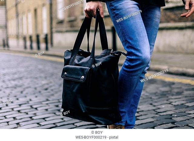 Young casual businessman carrying bag, low section