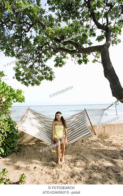 Portrait of a young woman sitting on a hammock
