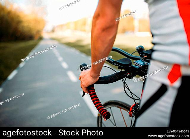 Male cyclist in sportswear, cycling on asphalt road. Male sportsman rides on bicycle. Workout on bike path