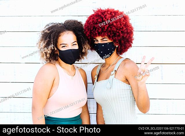 Two latin women with protection mask showing a victory symbol