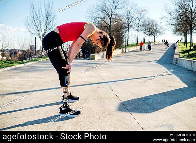 Exhausted sporty young woman with leg prosthesis standing on a walkway