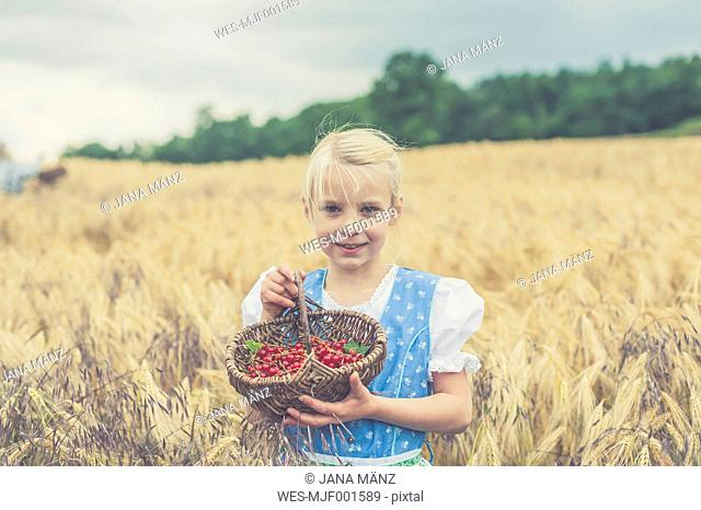 Germany, Saxony, portrait of smiling girl standing in a grain field with basket of red currants