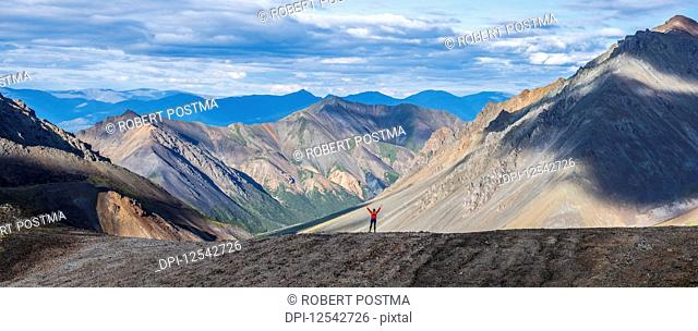 Woman standing with her arm raised while on a ridge line in Kluane National Park and Reserve; Haines Junction, Yukon, Canada