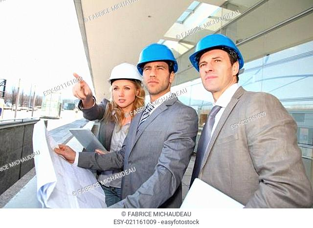 Construction engineers checking building site