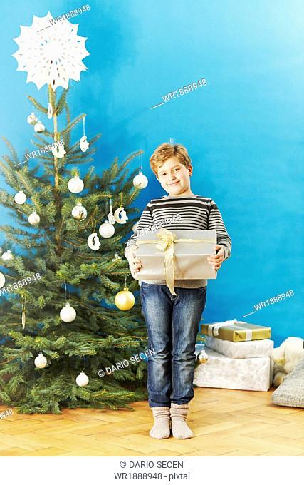 Little boy holding Christmas present, Munich, Bavaria, Germany