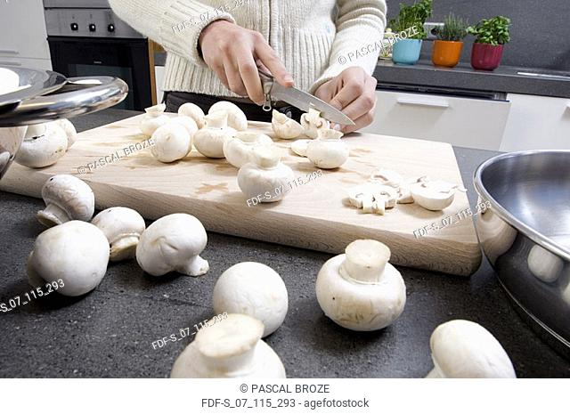 Mid section view of a woman cutting a mushroom on a cutting board