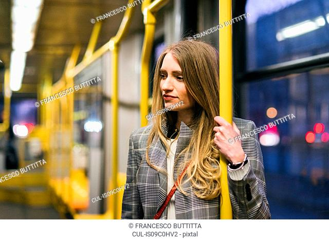 Young woman with long blond hair standing in train carriage at dusk