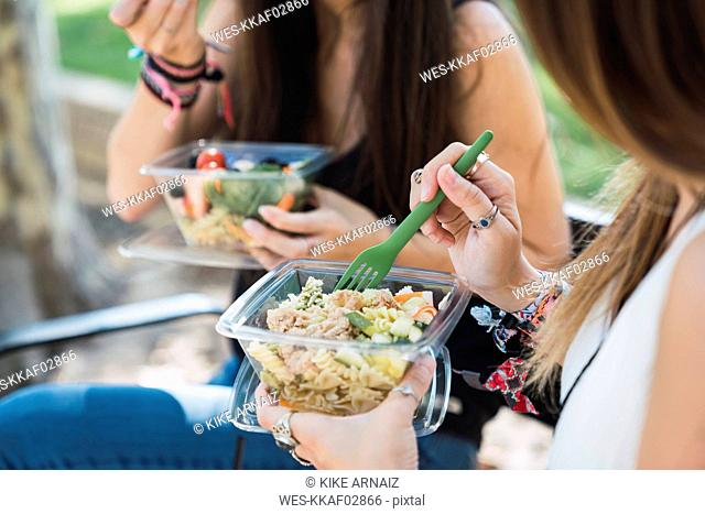 Girl friends sitting in a park, eating salad