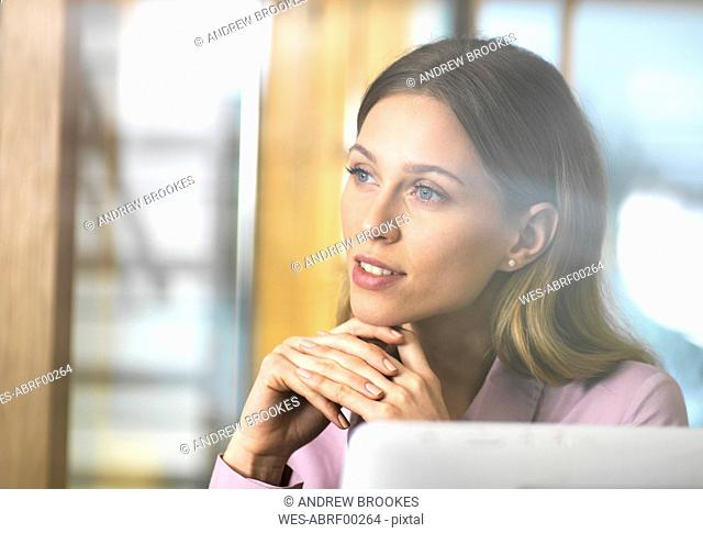 Confident businesswoman in office thinking