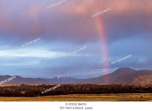 Rainbow above forest and mountains in Picabo, Idaho