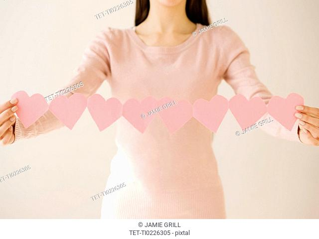 Woman holding string of cut out hearts