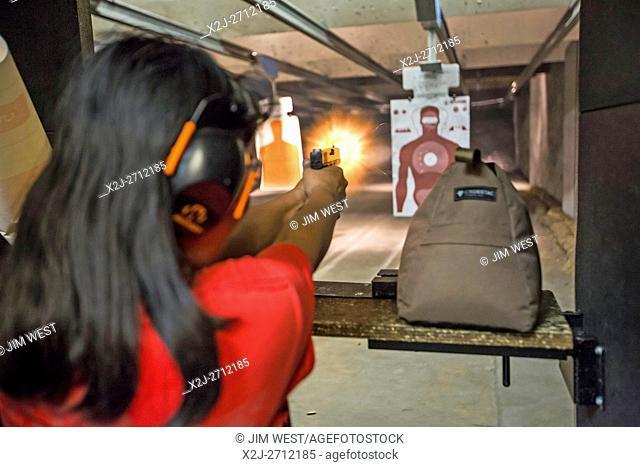Las Vegas, Nevada - A woman fires her handgun at the Discount Firearms + Ammo indoor shooting range