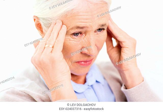 health care, pain, stress, age and people concept - face of senior woman suffering from headache