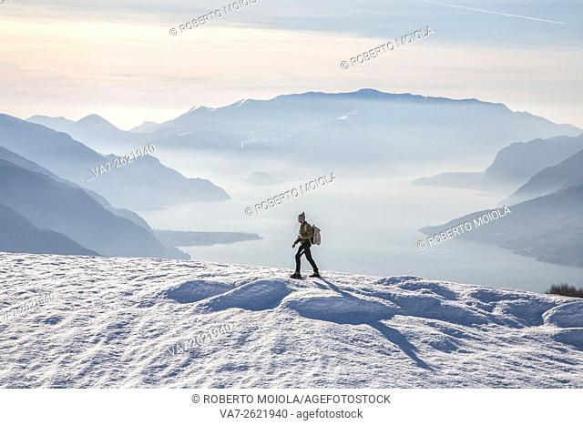 Winter view of Lake Como while a hiker proceeds with snowshoes Vercana mountains High Lario Lombardy Italy Europe