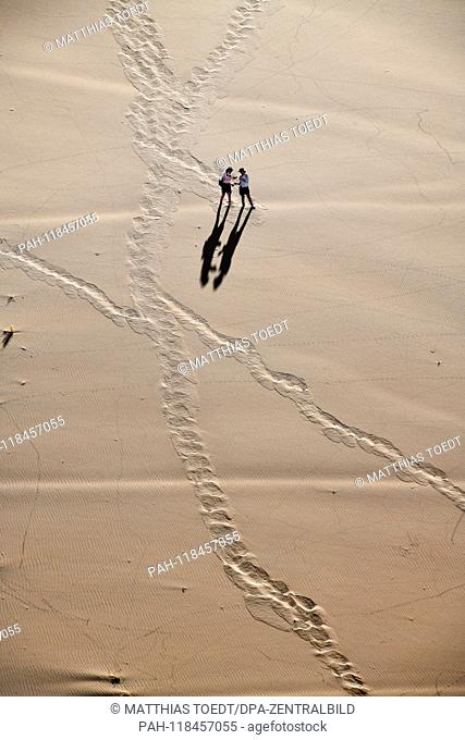 Two tourists walk down the high dunes to the Dead Vlei, taken on 01.03.2019. The Dead Vlei is a dry, surrounded by tall dune clay pan with numerous dead acacia...