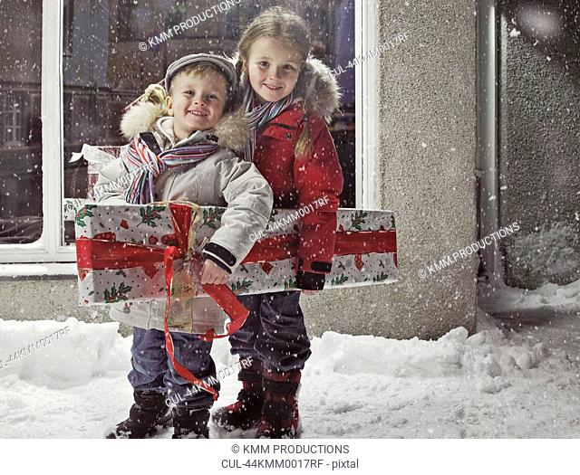 Children with Christmas present in snow