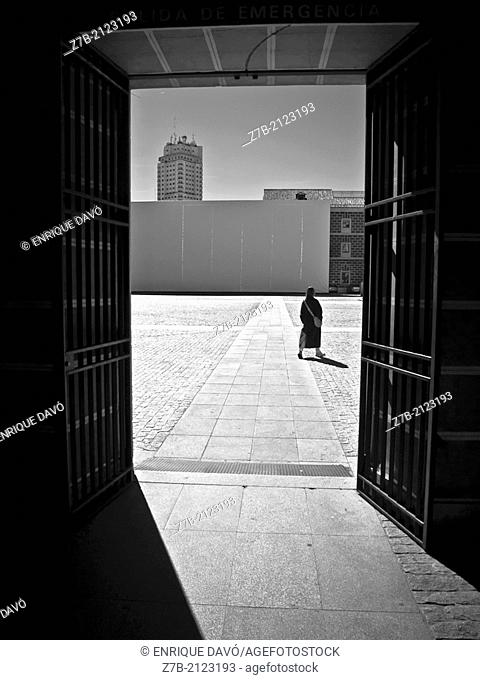 A woman walking in the courtyard of Conde Duque, Madrid, Spain
