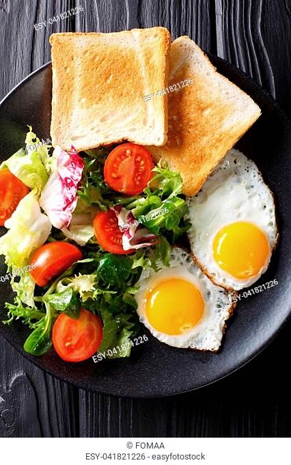 Organic food breakfast: fried eggs with fresh vegetable salad and toast close-up on a plate on the table. vertical top view from above