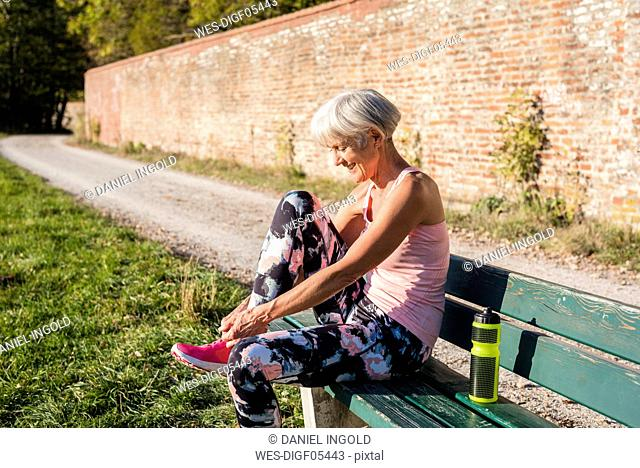 Smiling sportive senior woman sitting on a bench tying her shoes