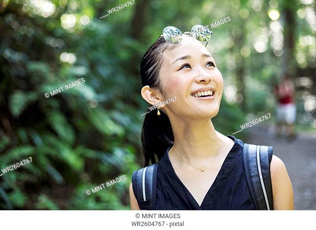 Portrait of a smiling young woman standing in a forest