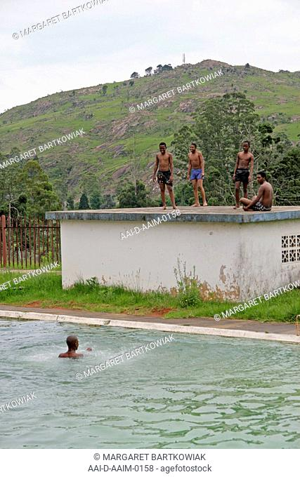 School boys standing on poolside rooftop, St Mark's School, Mbabane, Hhohho, Kingdom of Swaziland
