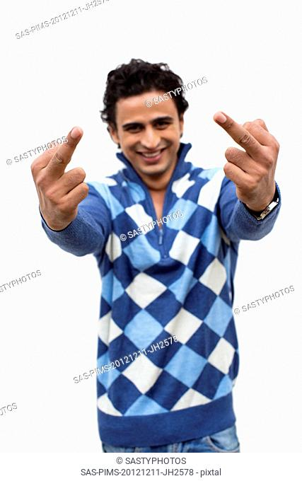 Portrait of a smiling man showing middle fingers