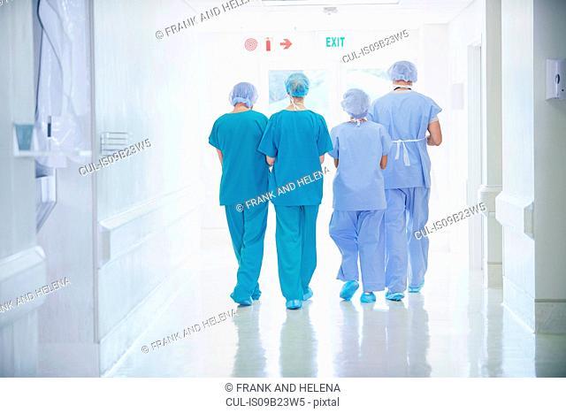 Rear view of four medical staff wearing scrubs walking in hospital corridor