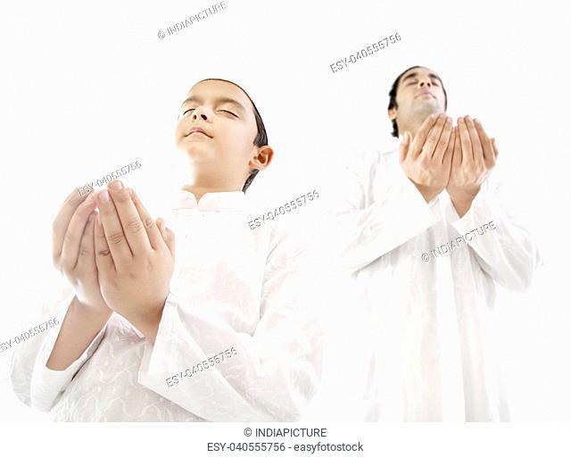Muslim man and his son praying