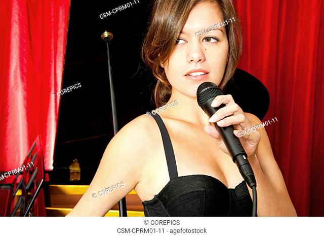 Beatuiful and mysterious looking brunette with a microphone is lead singer in front of a grand piano