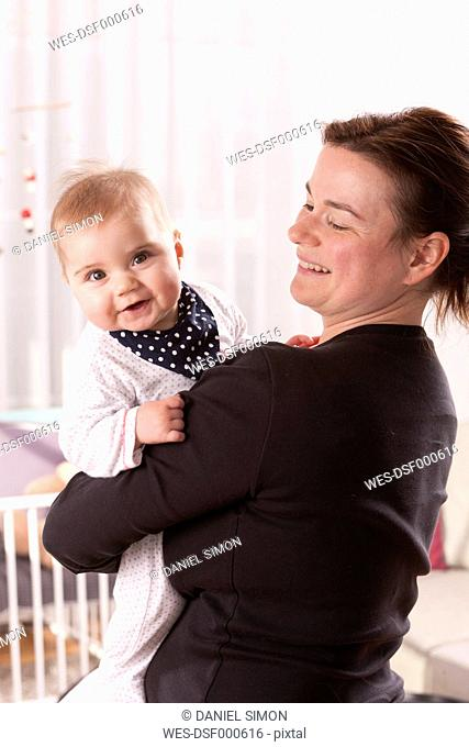 Happy baby girl on mother's arms
