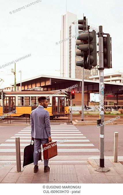 Businessman waiting by pedestrian crossing, Milano, Lombardia, Italy