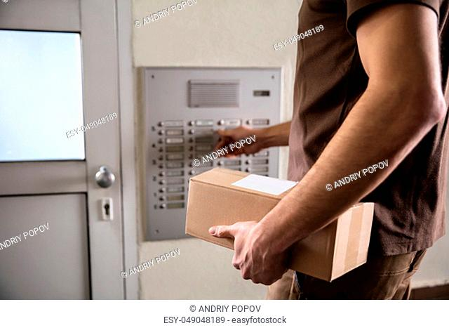 Mid-section Of Man Holding Cardboard Box Ringing Intercom