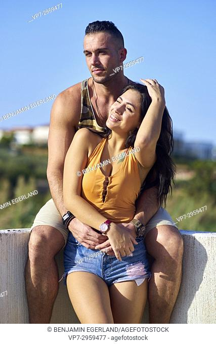 Thoughtful muscular man embracing happy girlfriend from behind. Greek ethnicity. In Hersonissos, Crete, Greece