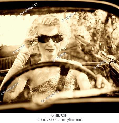 Retro woman behind steering wheel