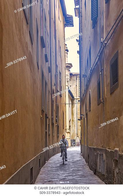 A lone cyclist on the Via de Giacomini in the back streets of Florence, Centro Storico, Firenze, Tuscany, Italy