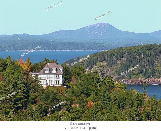 A house and islands are seen in the distance of a forest in Bar Harbor, Maine