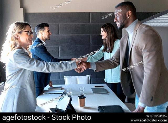 Business people doing handshakes while standing in board room at office