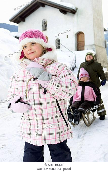 Children playing with sledge in snow