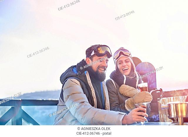 Snowboarder couple laughing, drinking cocktails on sunny balcony apres-ski