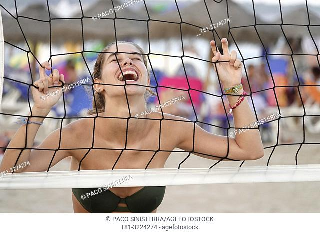 Girl playing beach volleyball, laughing. Peñíscola, Castellon Province, Spain