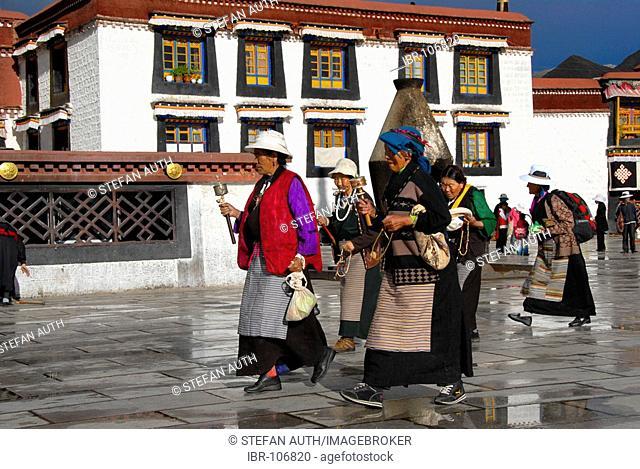 Tibetan pilgrims with prayer wheels at the Kora at Jokhang Temple Lhasa Tibet China