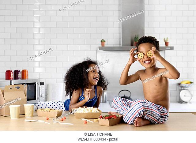 Little boy covering his eyes with cookies while sister watching him