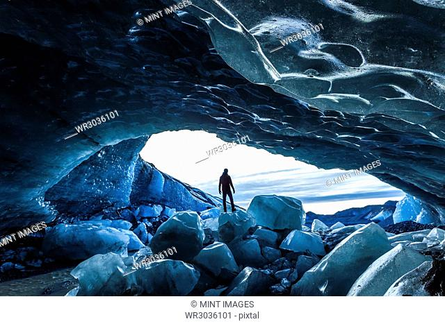 Rear view silhouette of person standing on ice rock at the entrance to a glacial ice cave