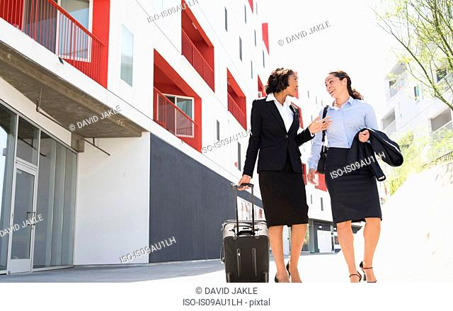 Two businesswomen walking along street, pulling suitcase